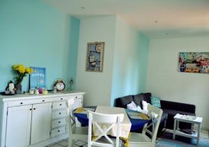 Mediterranean living room: blue walls, navy table, grey sofa, white furniture