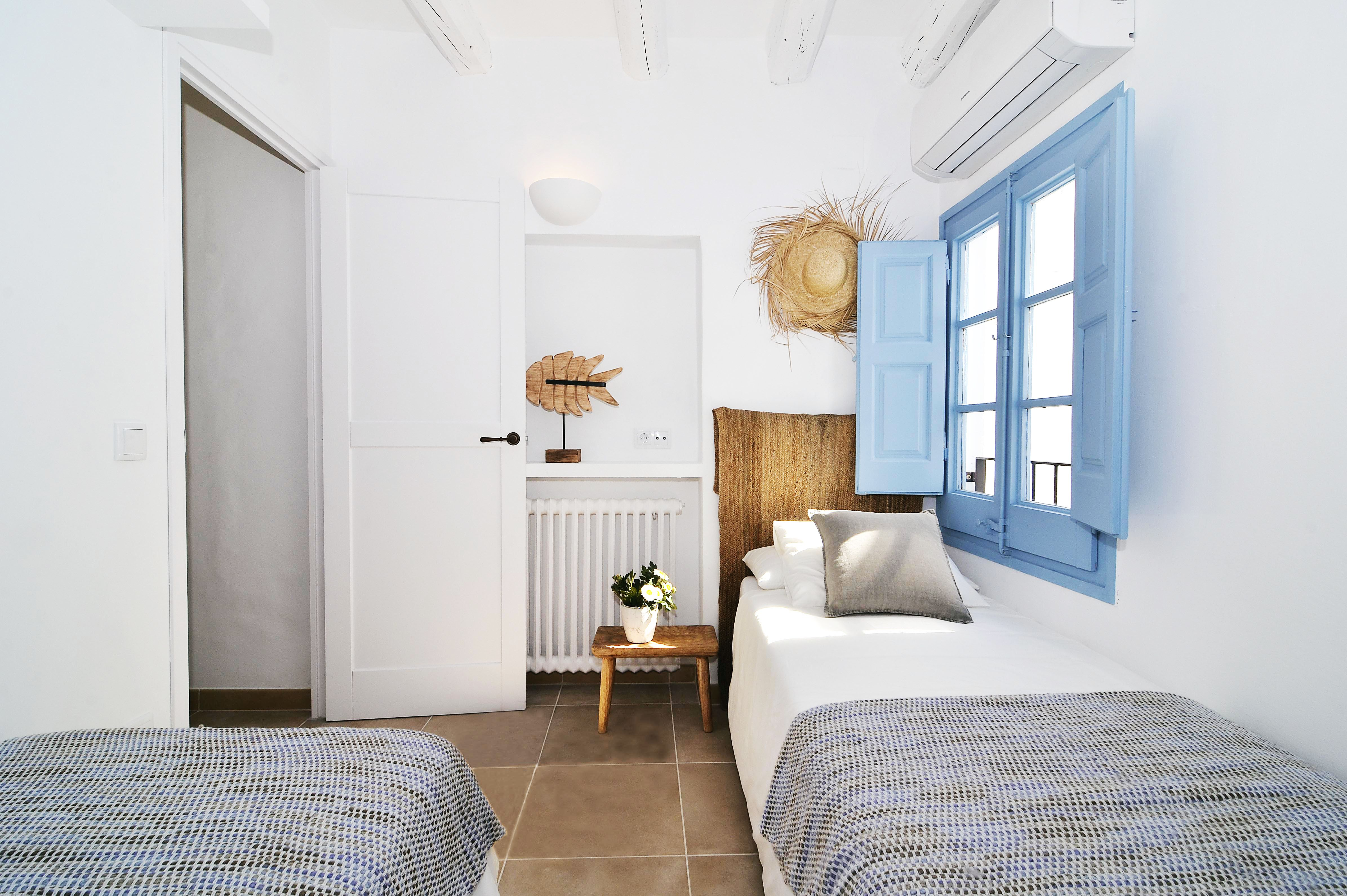 House tour: old fisherman's house in Sitges: bedroom with blue window