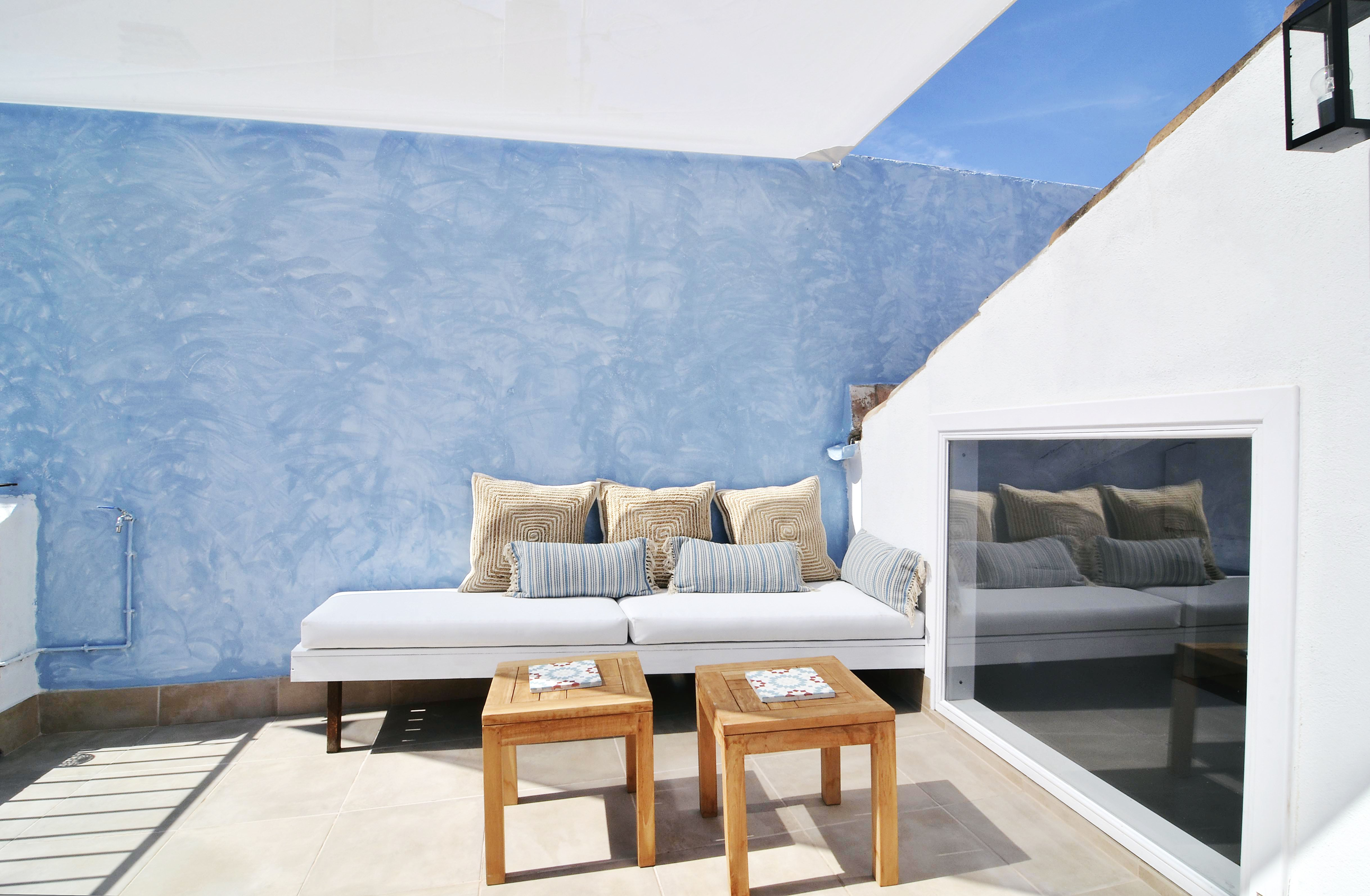 House tour: old fisherman's house in Sitges: sun-lit terrace with a blue wall