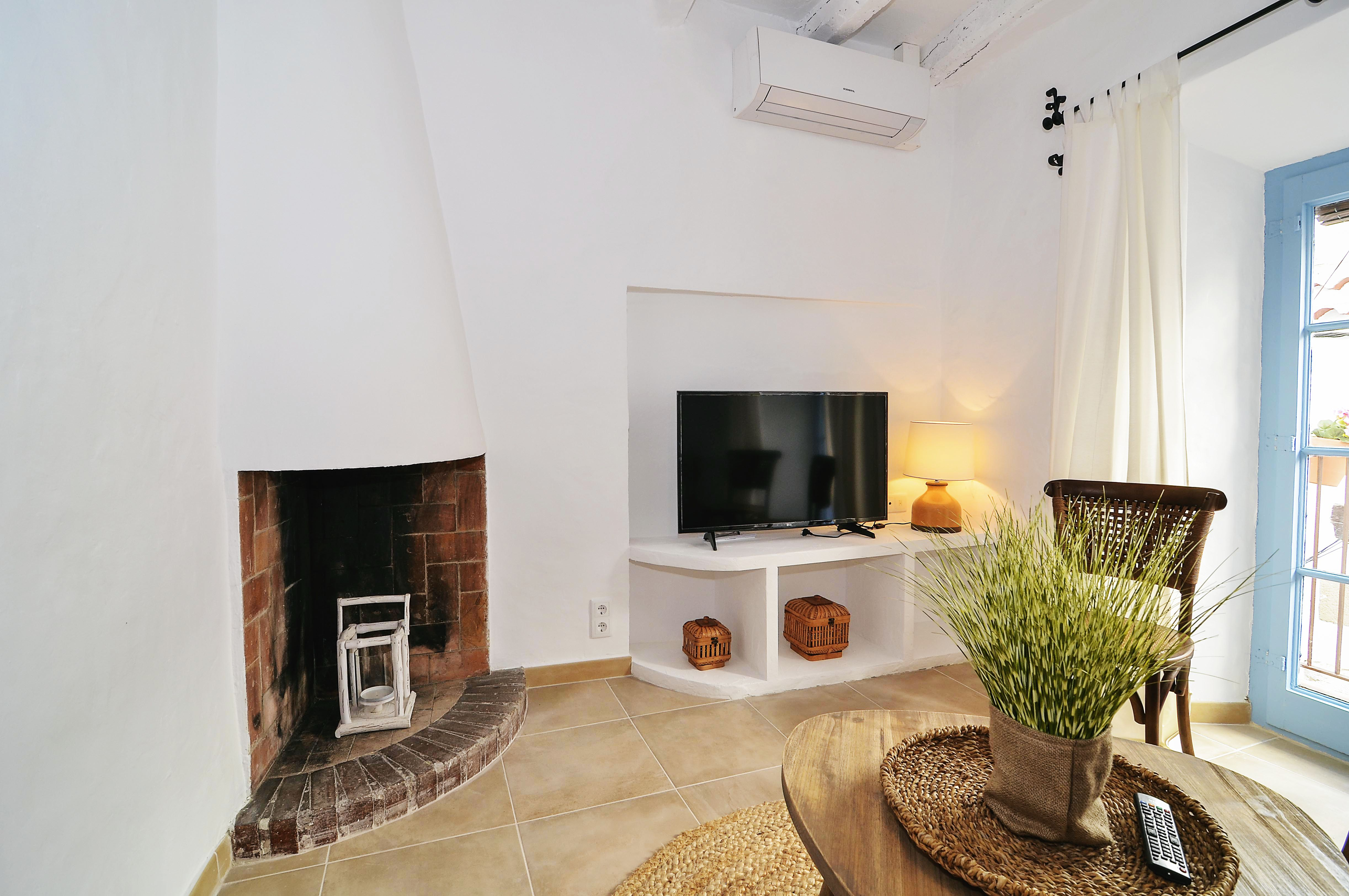 House tour: old fisherman's house in Sitges: sitting room with fireplace
