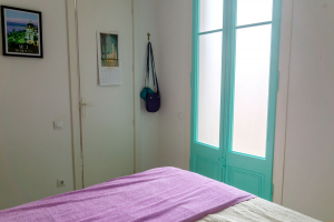 Turquoise balcony doors and lilac bed throw